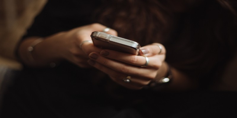 A close-up of a woman's hands using a smartphone.