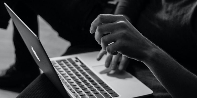 A black and white photo of a person's hands operating a laptop; JackpotCity Casino Blog