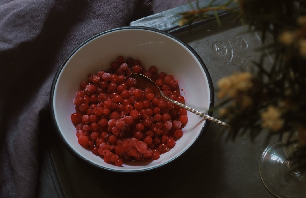 A bright red bowl of pomegranate seeds is one of many options to enjoy with an environmentally-friendly plant-based diet.