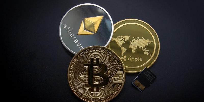 Münzen, die drei verschiedene Kryptowährungen darstellen sollen – Bitcoin, Ripple und Ethereum.