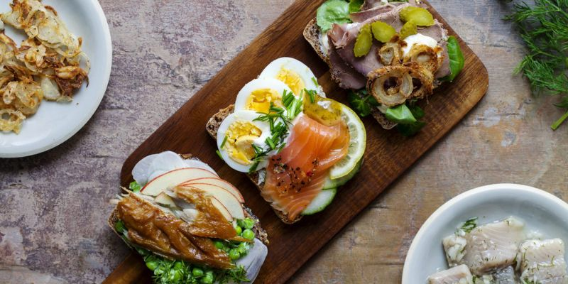 three plated Finnish sandwiches featuring salmon, crayfish, rye bread, and vegetables