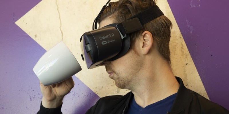 A man looking at a mug through a virtual reality headset he's wearing - Spin Palace Blog