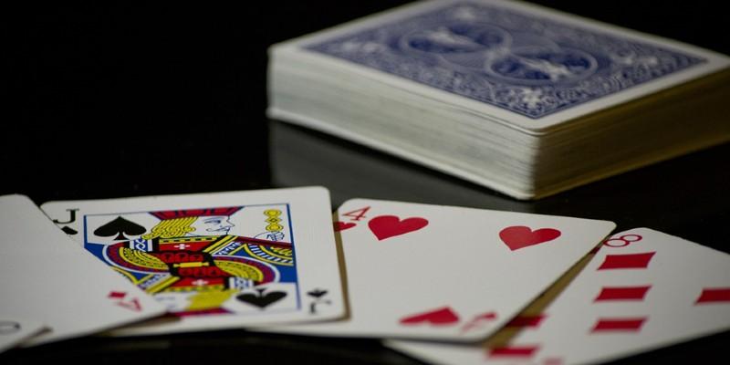 Vier offengelegte Karten und ein Kartendeck im Hintergrund; Spin Casino Blog