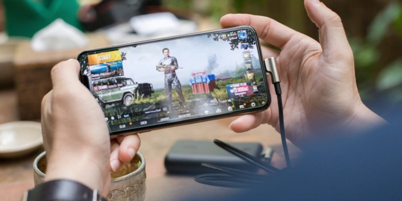 Person playing PUBG game on smartphone; Spin Casino Blog