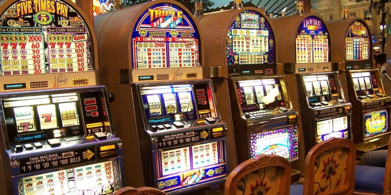 A line-up of five slot machines in a casino - Spin Palace Blog