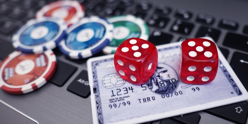 A stack of casino chips and a credit card on a laptop computer - Spin Palace Blog