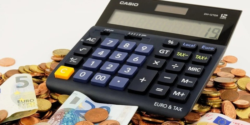 A calculator resting on a pile of money - Spin Palace Blog