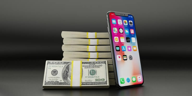 iPhone leaning against a stack of cash