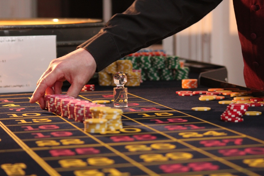 A dealer laying out casino chips on a Roulette table.