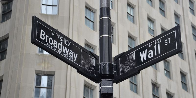 Street signs for Broadway and Wall Street