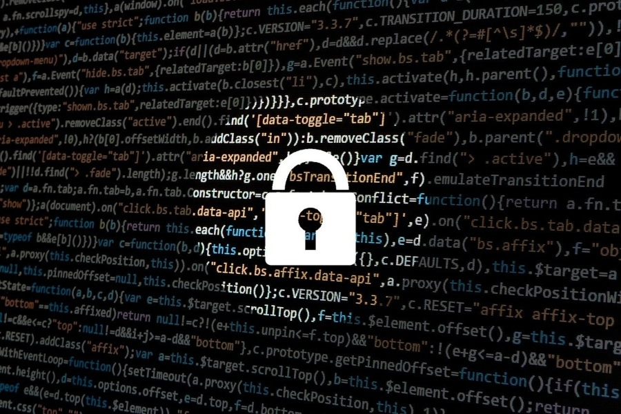 A cybersecurity padlock super-imposed over lines of computer code.