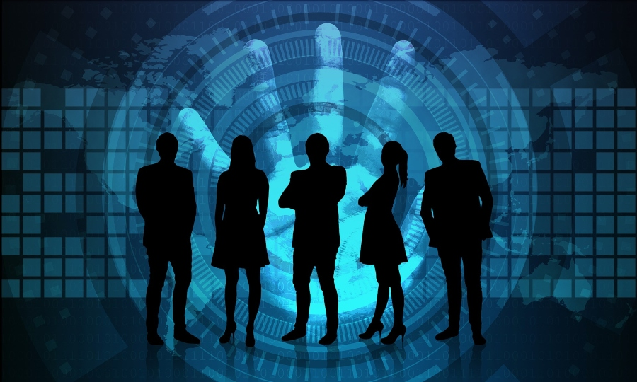 Silhouettes of people standing in front of cybersecurity imagery.
