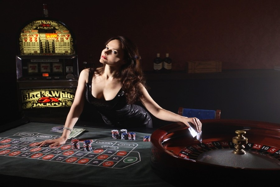 A female dealer running a Roulette table in a casino.