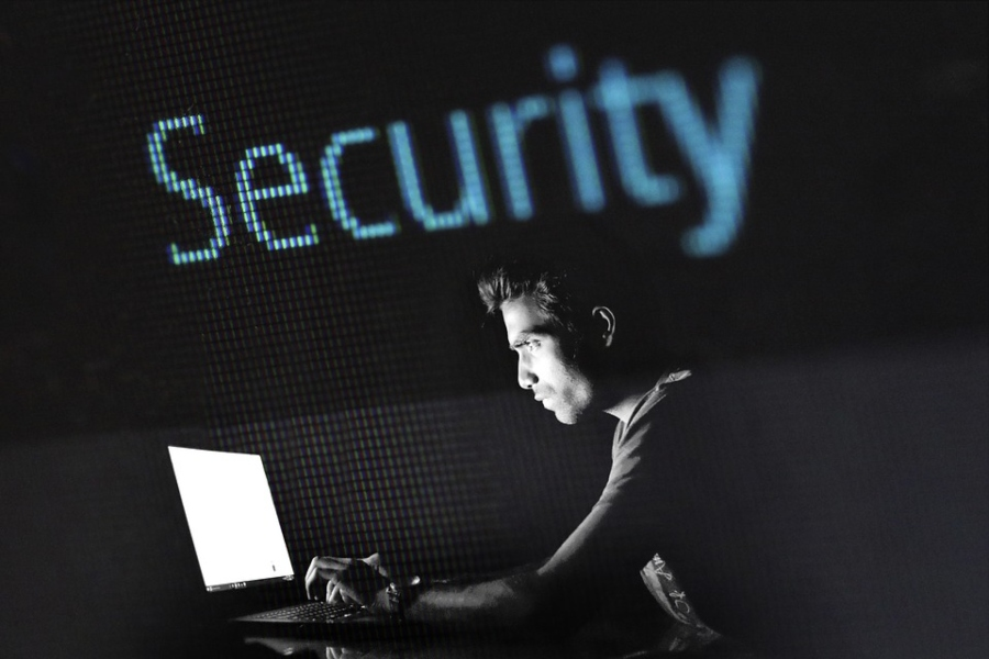 """A hacker works on a computer as the word """"Security"""" hangs above him."""