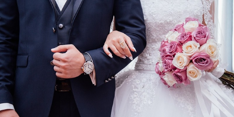 Bride and groom arm in arm with bouquet